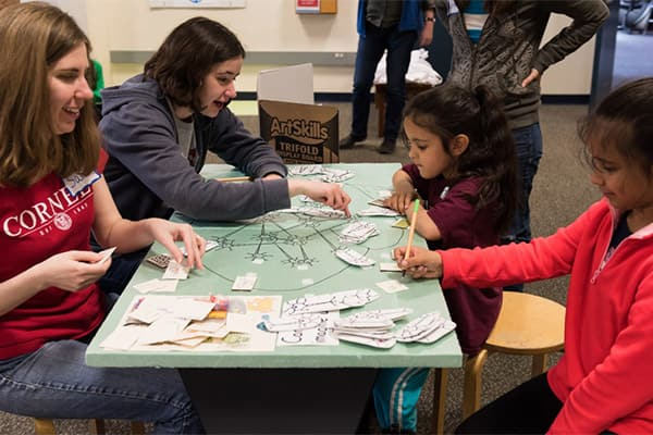 Graduate students working with children on science-related crafts